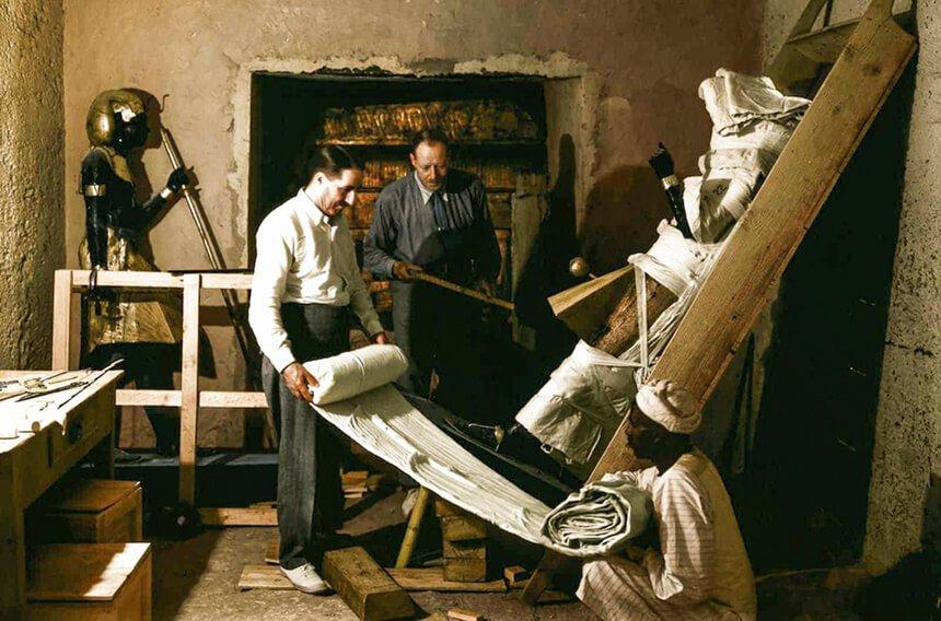 Howard Carter y un trabajador envolviendo la estatua de un centinela para su transporte